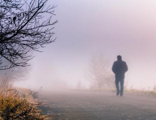 man-walking-along-foggy-road